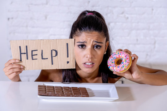 Sad woman on diet holding a sign help resisting temptation to eat chocolate and donuts