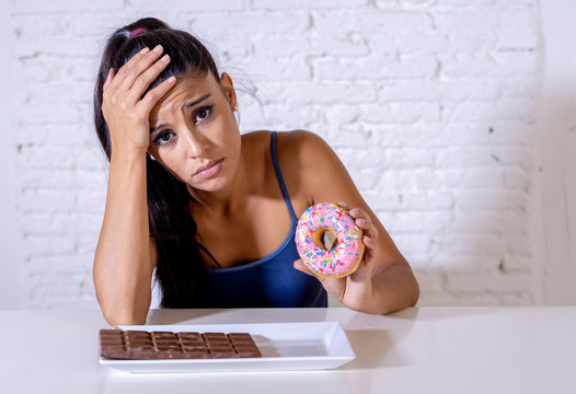 Pretty latin woman looking at chocolate and donuts tired of diet restrictions