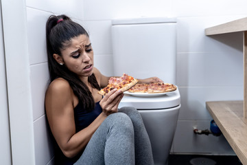 Young beautiful bulimic woman sitting on the bathroom floor eating pizza looking guilty
