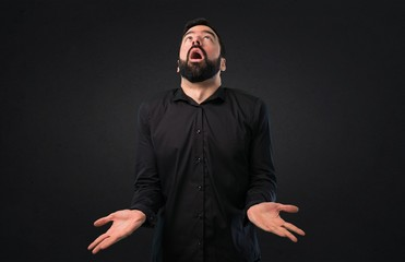 Handsome man with beard pleading on black background