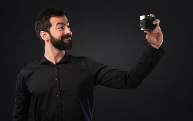 Handsome man with beard making a selfie on black background