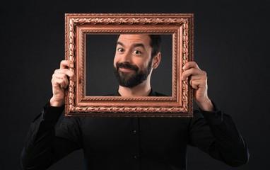 Handsome man with beard holding a framework on black background