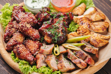 Big plate with grilled meat and sauces on dark wooden table
