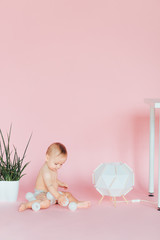 Baby. Newborn in the diaper. Isolated. Toddler playing with toy. Pink background