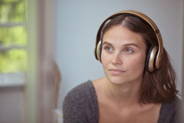 Close-up portrait of a beautiful young woman listening to music on her golden headphones on ears.