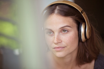 Close-up portrait of a beautiful young woman with golden headphones on ears.