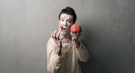 Terrorific zombie eating a brain.  Halloween holidays
