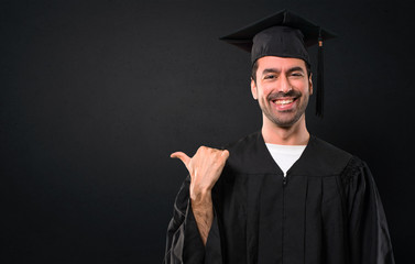 Man on his graduation day University pointing to the side with a finger to present a product or an idea while looking forward smiling on black background