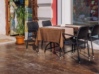 A table with a chair chairs near the window of a summer cafe.
