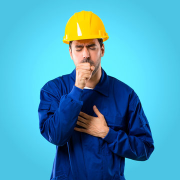 Young workman with helmet is suffering with cough and feeling bad on blue background