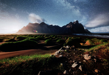 Fantastic west of the mountains and volcanic lava sand dunes on the beach Stokksness, Iceland. Colorful summer night Iceland, Europe. Deep sky astrophoto.