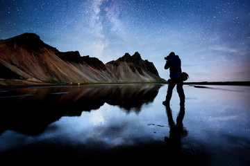 Photo sur Aluminium Reflexion Amazing mountains reflected in the water at starry night. Stoksnes, Iceland. Silhouette of the nature photographer in the frame