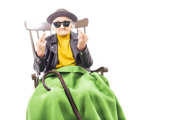 Old woman with sunglasses sitting on a chair.