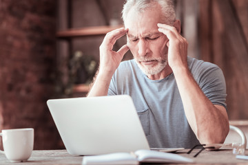 Distressed. Close up of tired elderly man touching his head while placing his elbows on the table and keeping his eyes closed Wall mural