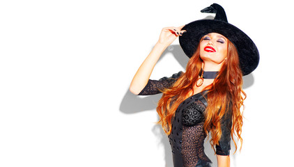 Halloween. Sexy witch with bright holiday makeup. Beautiful young woman posing in witches costume over white background Fototapete