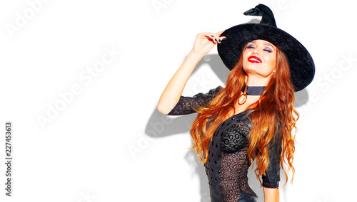 Halloween. Sexy witch with bright holiday makeup. Beautiful young woman posing in witches costume over white background