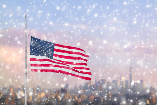 American flag and blurred skyline of Manhattan in the snowfall. New York city. Winter concept.