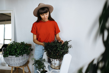 Stylish woman gardener growing plants for garden. Cheerful florist with beautiful face and smile wearing red t shirt and hipster hat working in flower shop.