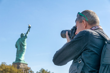 Male photographer taking pictures of Statue of Liberty in New York City