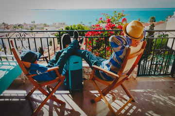 father and son relax on balcony terrace with suitcase, travel concept