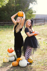 Two girl in carnival costumes with Halloween pumpkins  at country farm on warm autumn day.