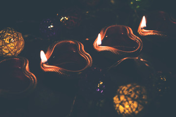 Beautiful diwali diyas at night with flowers, lighting series and gifts, moody background