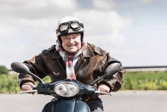 Active senior man speeding on his motor scooter