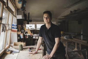 Portrait of smiling carpenter with bottle of beer in workshop