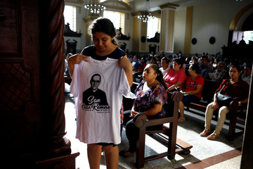 A woman tries a t-shirt of the late Archbishop of San Salvador, Mons. Oscar Arnulfo Romero during a mass at the Metropolitan Cathedral in San Salvador