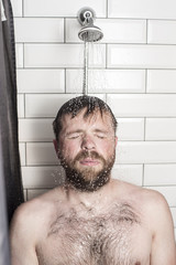 Tired bearded man relaxes in the bathroom standing in the shower under running warm water.