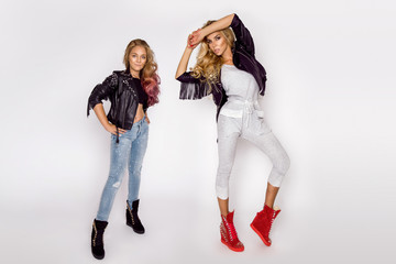 Beautiful blond girls, mother with daughter in jeans clothing on a white background in the studio.