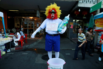 A dressed-up man collects alms during a vegetable festival in Chinatown at Bangkok