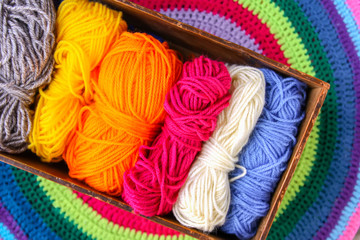 Knitted mat and colorful skeins of wollen yarn