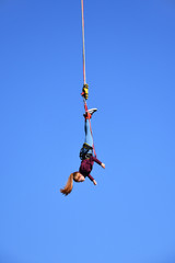 Bungee jumping. Beautiful young girl with long ponytail hanging on a cord high in the blue sky