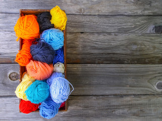 Balls of bright woolen yarn in a wooden box on old wood background