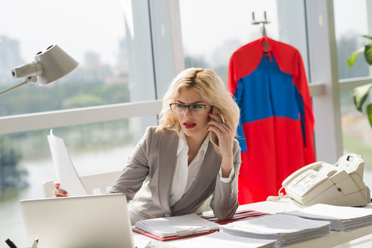 Attractive Caucasian businesswoman talking on smartphone while sitting at office desk with papers and laptop, superwoman costume hanging behind