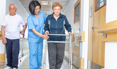 Asian doctor helping elder woman with walker and man in hospital aisle