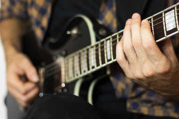 Young man playing on electric guitar, music concept