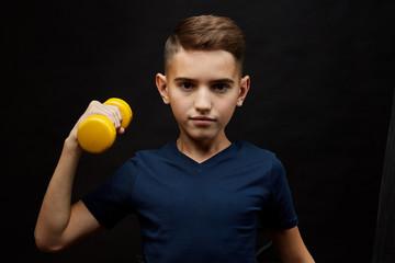 boy fitness lifts dumbbells. happy childhood, children sports