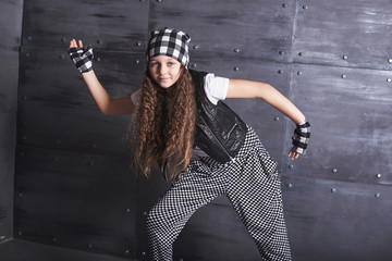 Young beautiful girl dancing in a trendy clothes on a grunge background