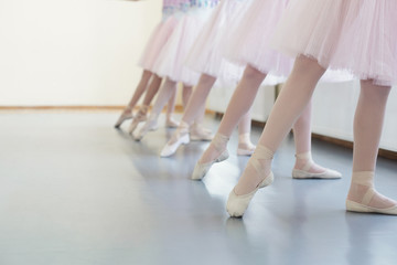 Ballerinas in pointe shoes stretching legs before dance lessons