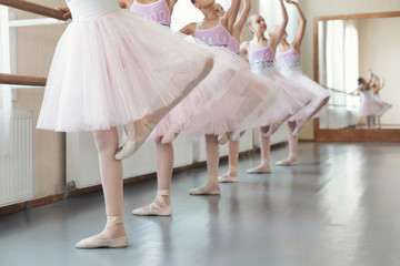 Girls training dance moves near ballet barre