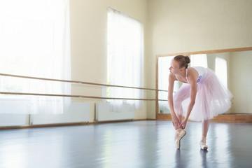 Ballet dancer tying pointe shoes in light studio