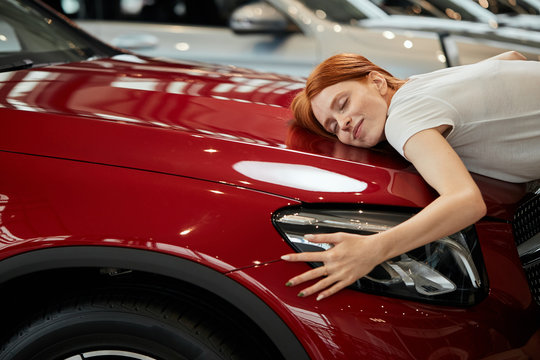 Dreams come true today. Young emotive cute woman with amazed expression, embracing her new cargently at car show room. Husband bought her new car for b-day.