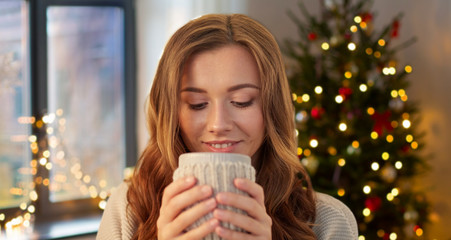 Fototapete - holidays and people concept - happy young woman with cup of coffee or tea at home over christmas tree lights background