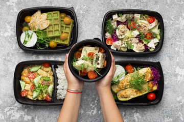 Plastic containers with delicious food on gray background