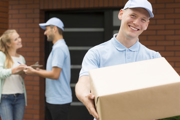 Handsome courier in blue uniform holding big brown package and smiling