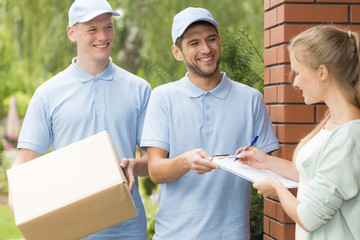 Two handsome couriers in blue uniforms delivering a parcel to a young pretty woman