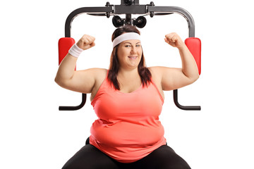 Corpulent woman showing muscles with an exercising machine