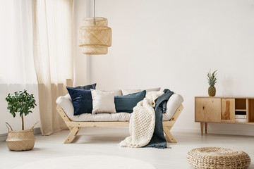 Light lounge with pillows and two blankets placed in white sitting room interior with window with curtains, straw lamp and fresh plant on floor in real photo